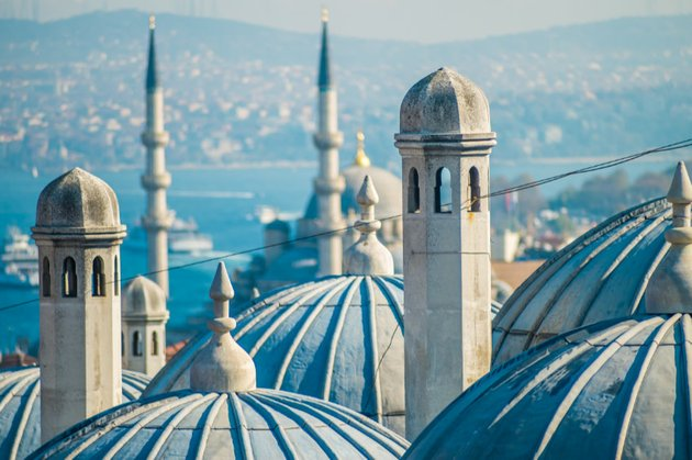 Minarettes and domes of a mosque with water in the background