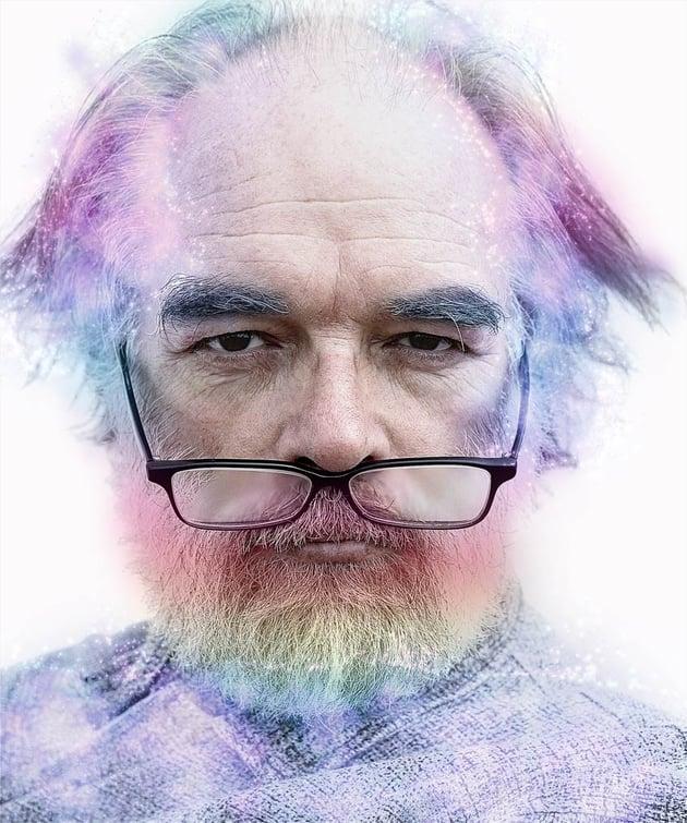 Man with rainbow coloured hair beard and eyebrows with sparkles added to hair and shirt