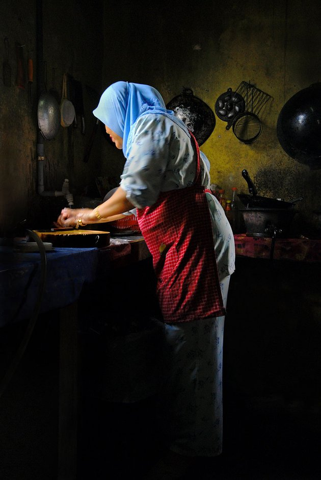 Malaysian Lady Prepares Food in the Kitchen