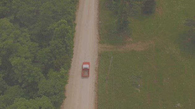 Aerial photograph of a red truck driving on a rural road