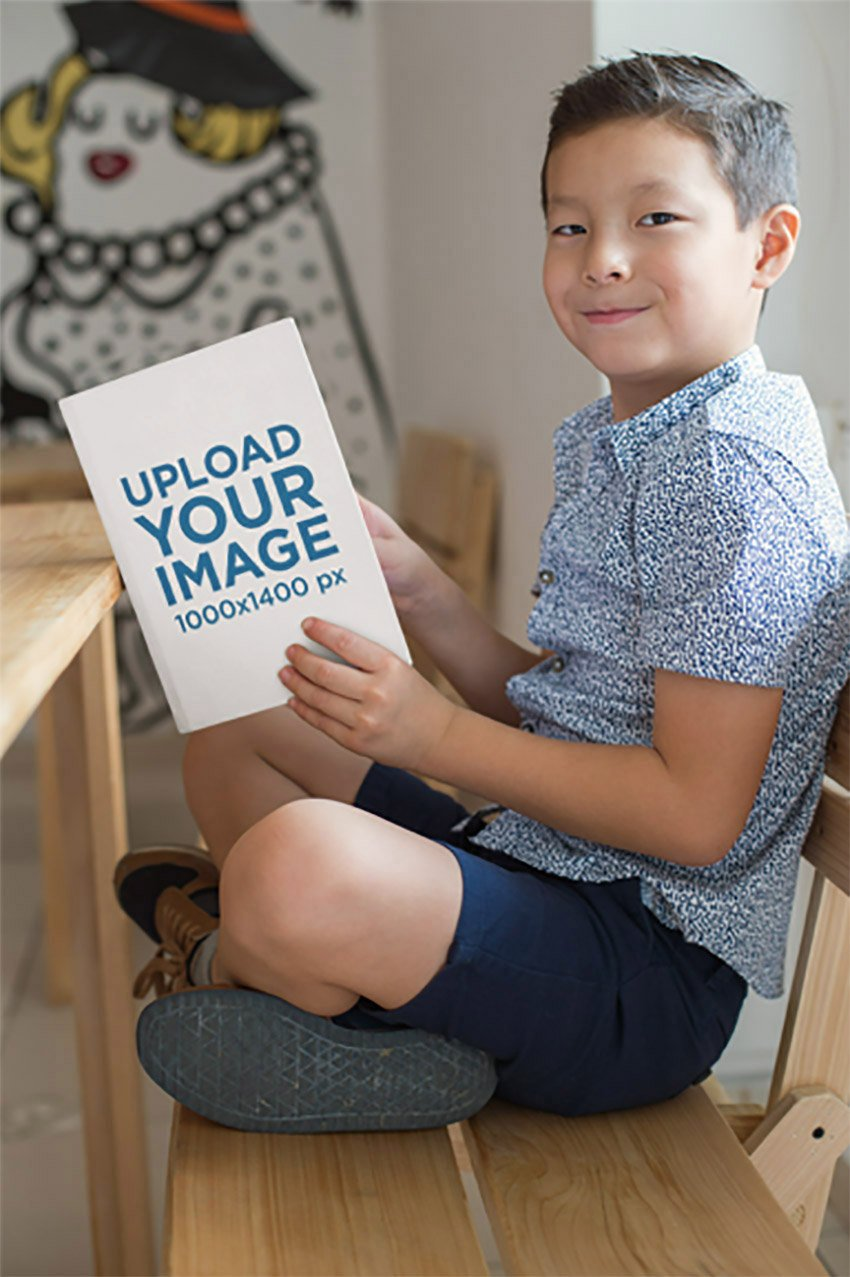 Book Mockup of a Little Boy Reading and Smiling