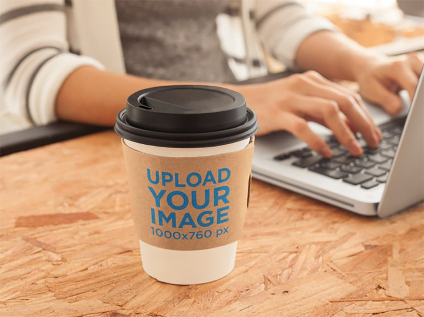 Mockup of a Coffee Cup Sitting Next to a Macbook Pro at an Office