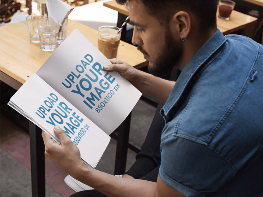 Mockup of a Young Man With Beard Reading a Magazine While at a Coffee Shop