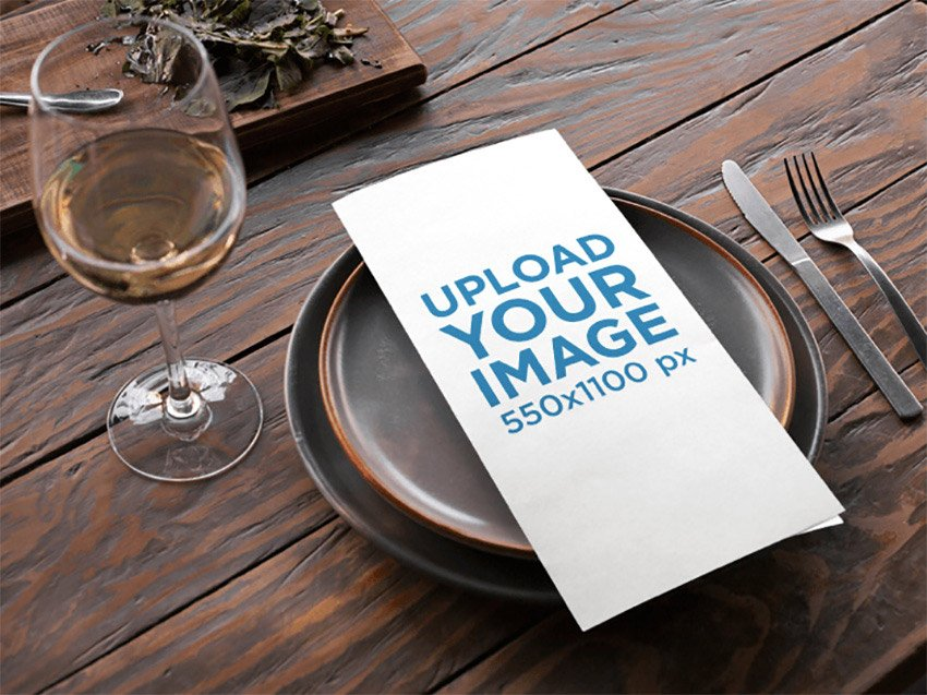 Menu Template Lying Over Dishes Near a Glass of White Wine on a Wooden Table