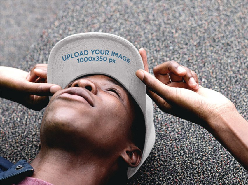 Hat Mockup of a Black Guy Lying on the Ground Looking Up