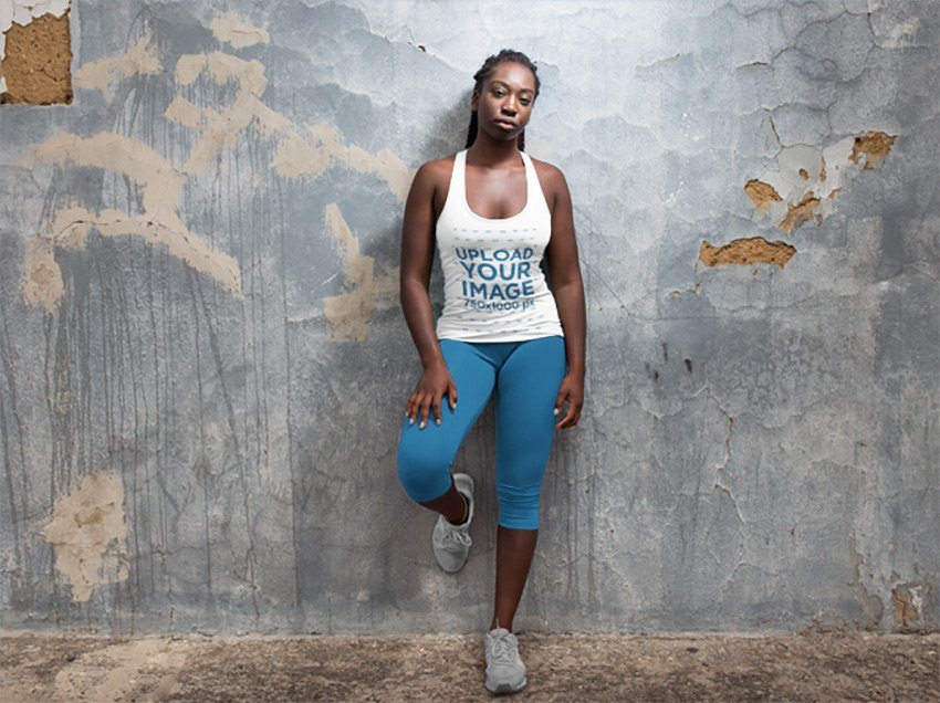 Runner Woman with Dreadlocks Wearing a Tank Top Mockup While Lying Against a Concrete Wall