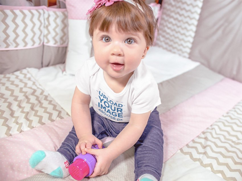 Beautiful Baby Girl Sitting Down Happy While Wearing A Onesie And Playing With Her Purple And Pink Toy Mockup