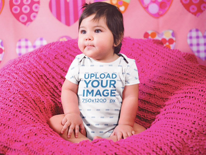 Beautiful Little Baby Girl Sitting On A Pink Sofa While Wearing A Onesie