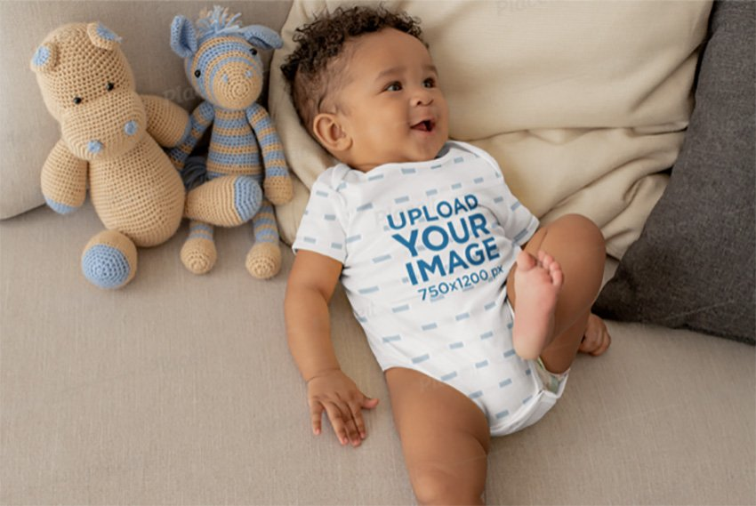 Onesie Mockup of a Cute Baby Boy Lying in Bed with Stuffed Animals
