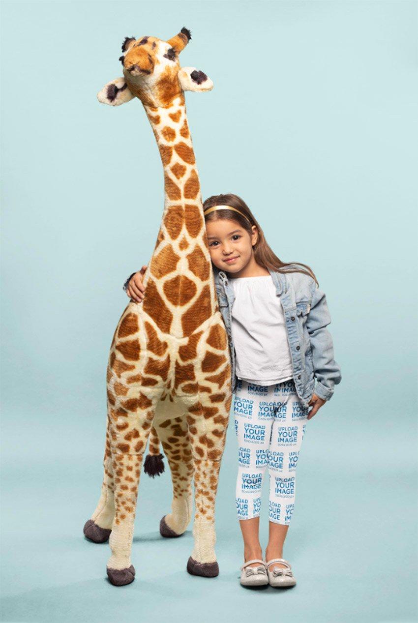 Leggings Mockup of a Cute Little Girl Hugging a Plush Giraffe