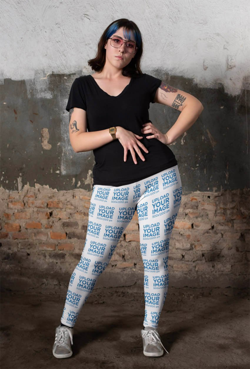 Mockup of a Tattooed Woman Wearing Plus Size Leggings Against an Old Wall
