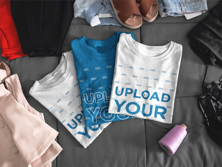 Mockup of Three T-Shirts Lying Folded on a Bed