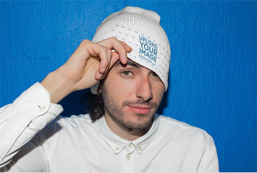 Mockup of a Playful Man Wearing a Beanie Against a Blue Wall