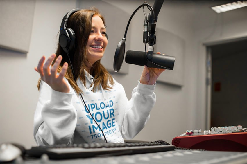 Mockup of a Woman Wearing a Hoodie at a Radio Booth