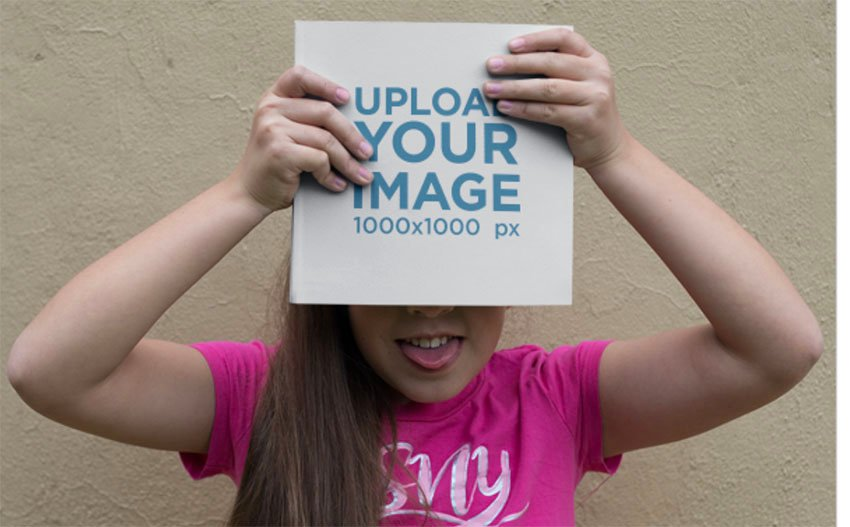 Little Girl Being Funny while Holding a Square Book Mockup