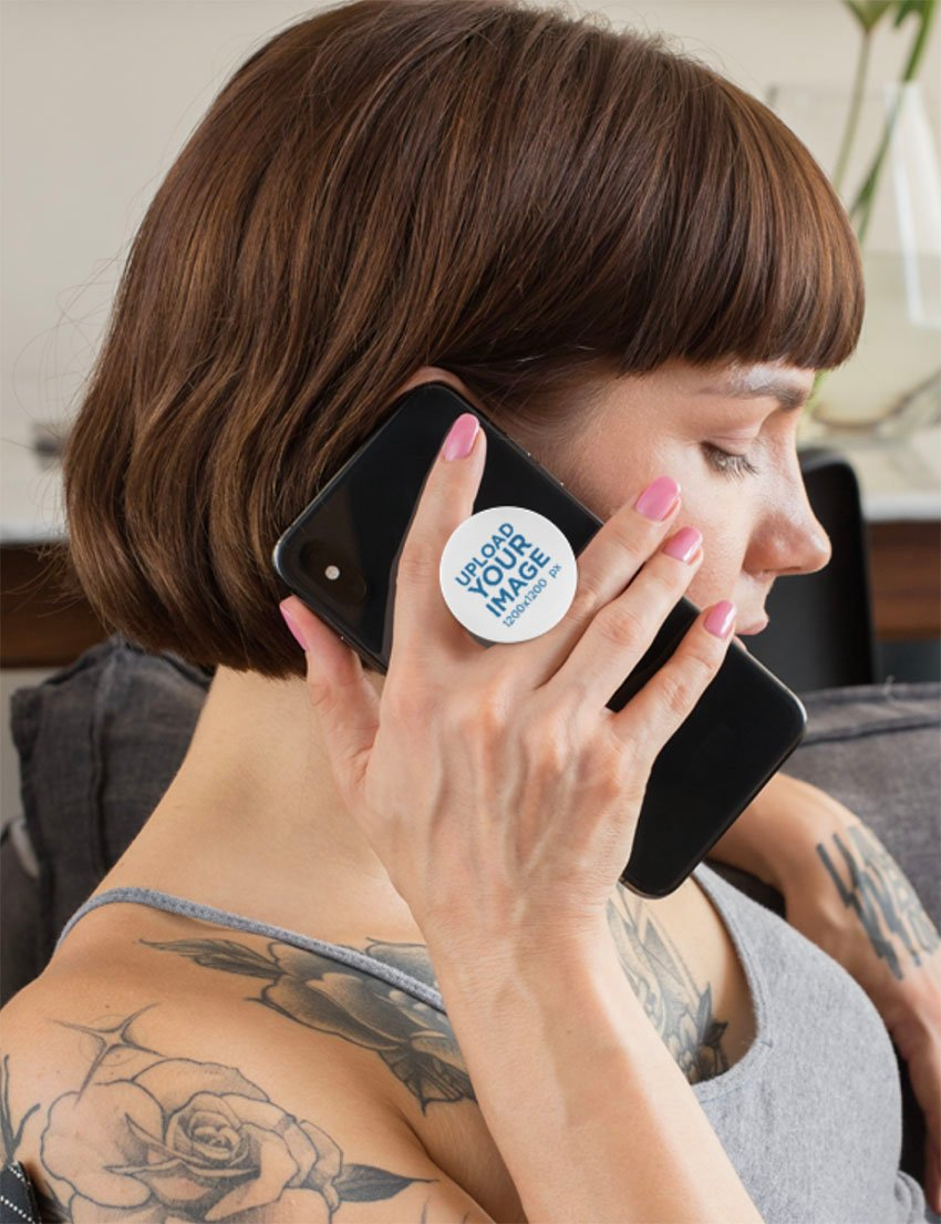 Blank Phone Grip Mockup Featuring a Woman With Tattoos Sitting on a Couch