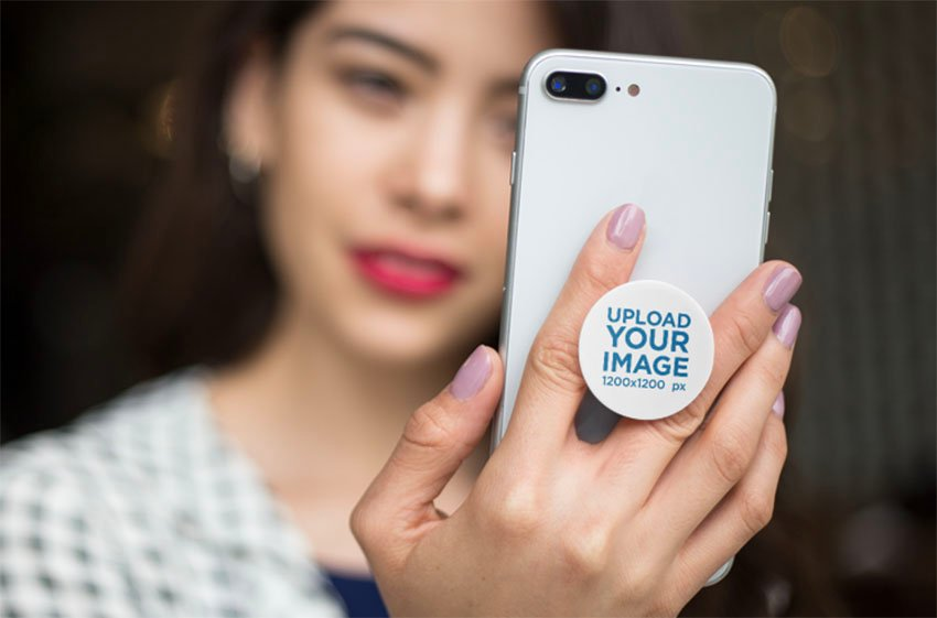 Blank Phone Grip Mockup Held by a Woman Staring at Her Screen
