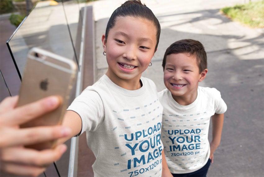 Kids T-Shirt Mockup Featuring Children Taking a Selfie