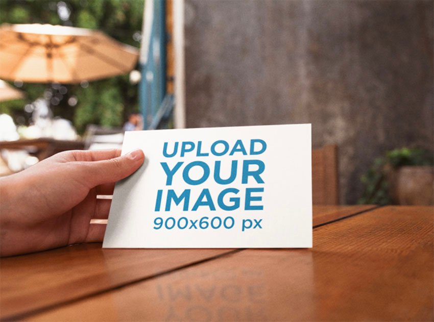 A6 Postcard Mockup Template on a Wooden Table at a Cafe