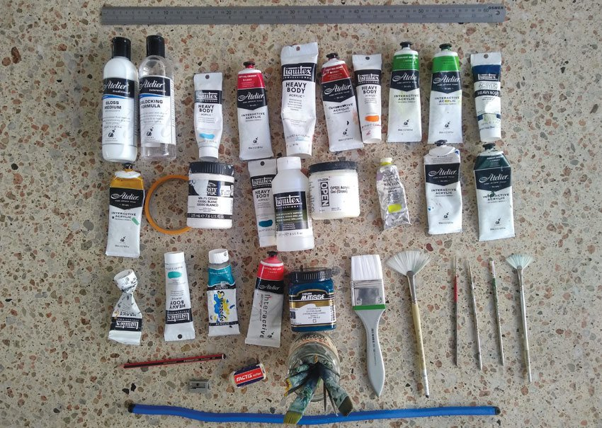 selection of paints and brushes for a realism painting