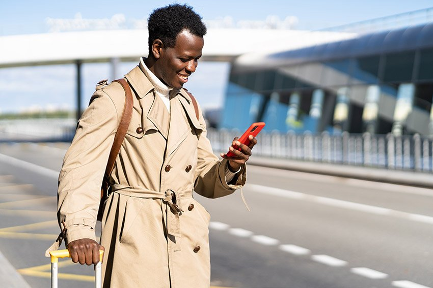 Man Hailing taxi from phone at airport