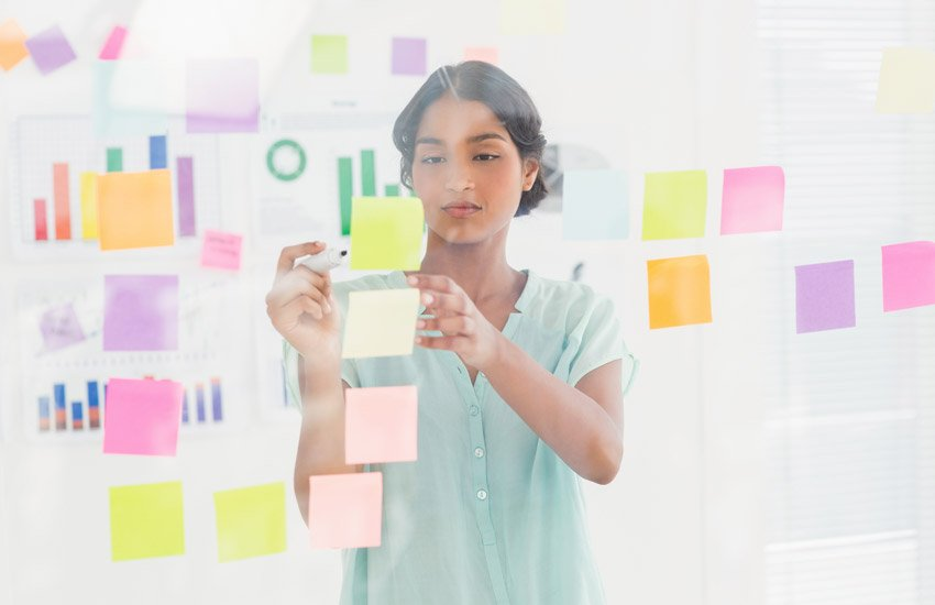 Concentrated businesswoman looking post its on the wall in the office