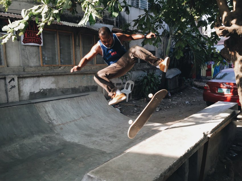 Person performing a skateboard trick in a backyard half-pipe