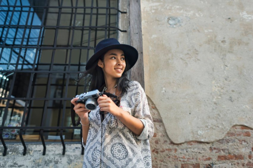 woman in a hat taking pictures