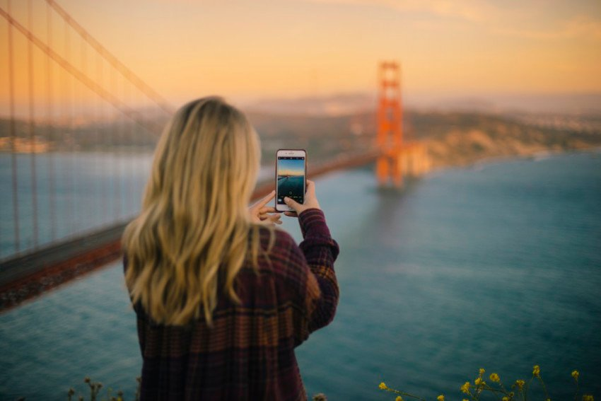 Photograph of a person taking a smartphone image of the Golden Gate Bridge in San Francisco California