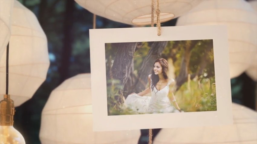 Picture of woman in wedding dress hangs in front of paper lanterns