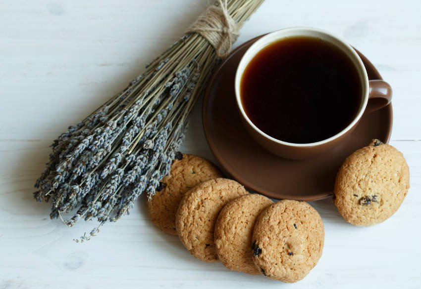 Lavender cookies and cup of tea on white wooden background
