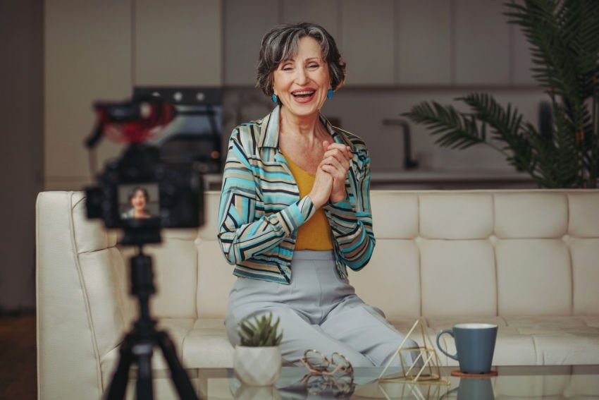 Senior woman vlogger on camera, in a liveing room setting
