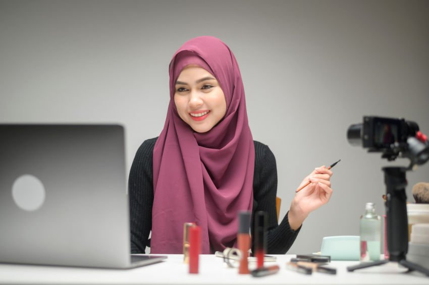 Young Muslim woman demonstrate makeup technique on laptop video