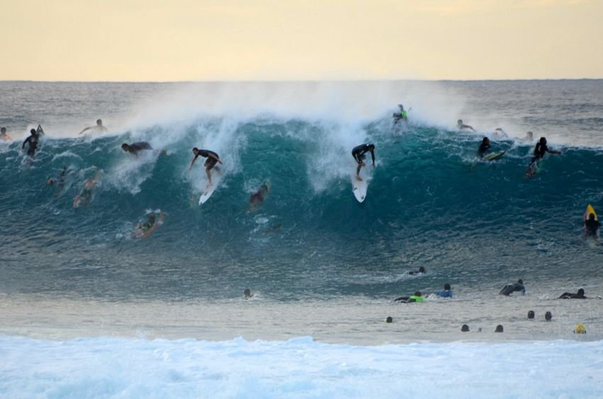Surfers sharing a wave