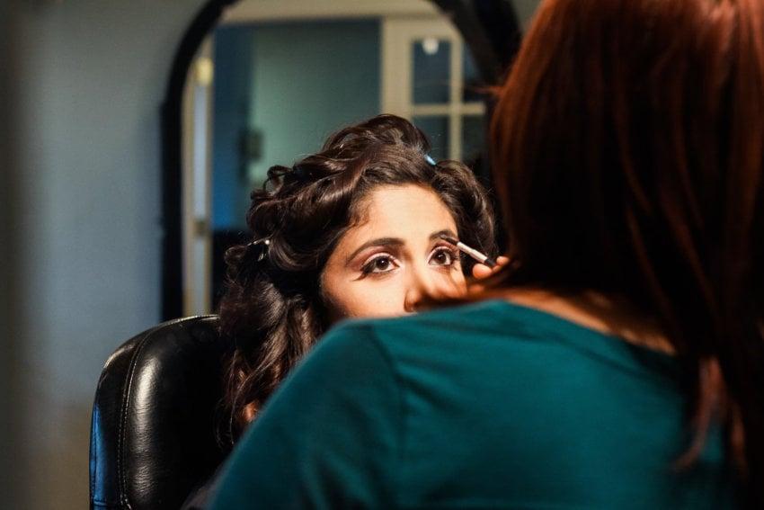 A makeup artist applying makeup to a woman