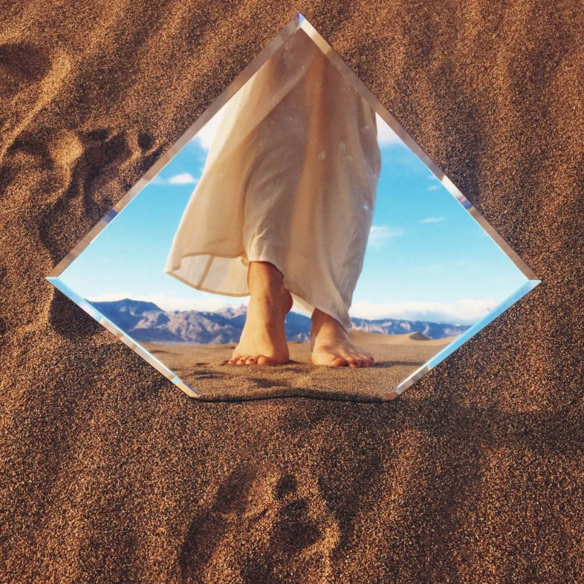 Mirror in the sand, with a woman's feet