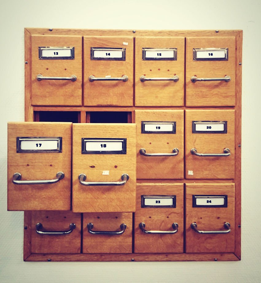 Card catalogue filing cabinet set into wall, two open drawers