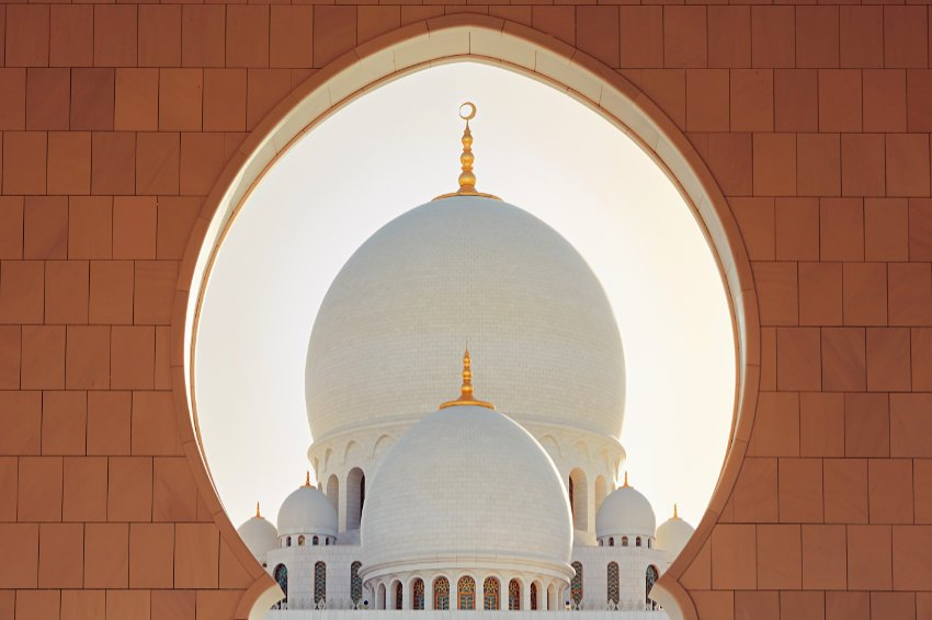 Dome of a mosque framed by scalloped archway