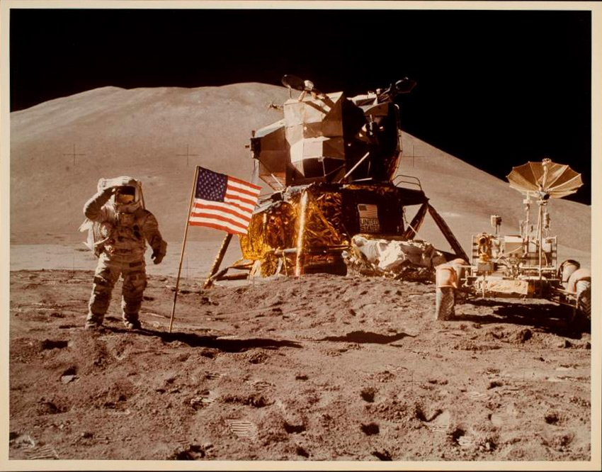 Astronaut on the moon beside the American flag and space vehicles
