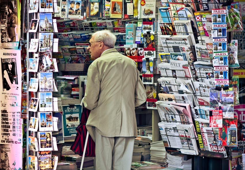 Newsagent shop with racks of newspaper and magazines