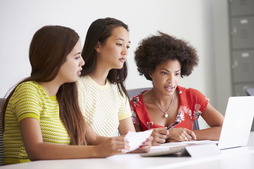Three women working together in a design studio