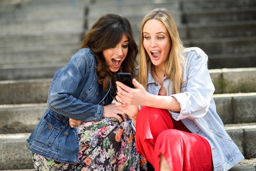 Two women reacting happily to something on their phone