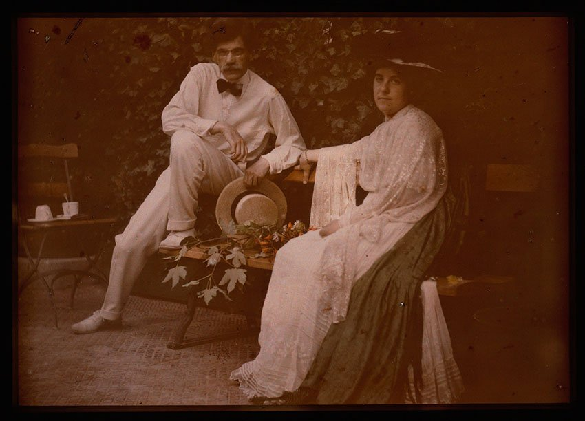 Autochrome of a man and woman sitting on a bench in a garden
