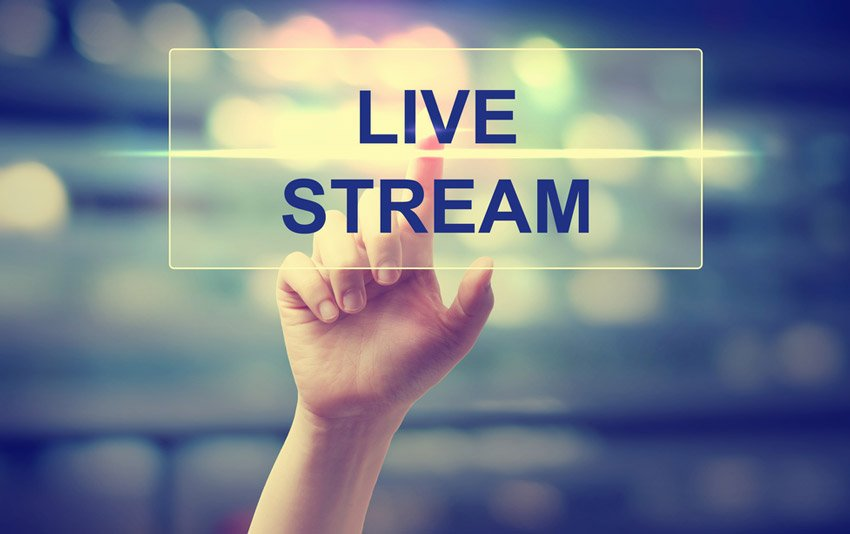Hand pushes Live Stream button