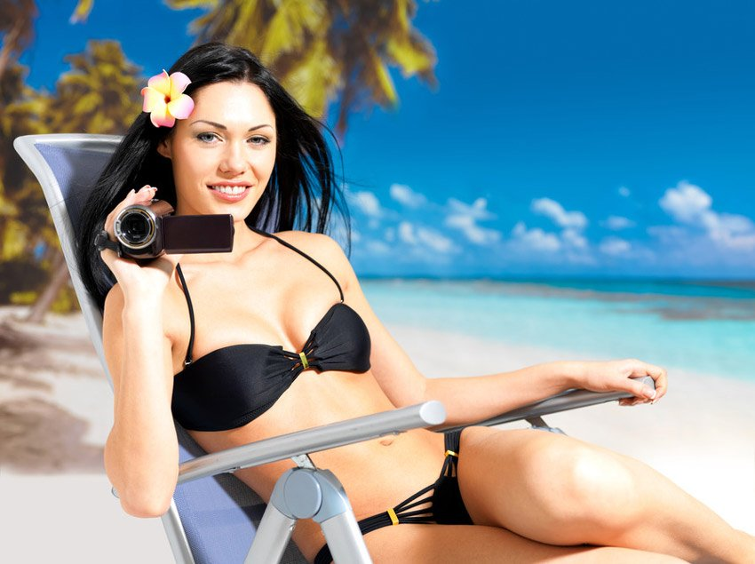 Woman on beach with video camera