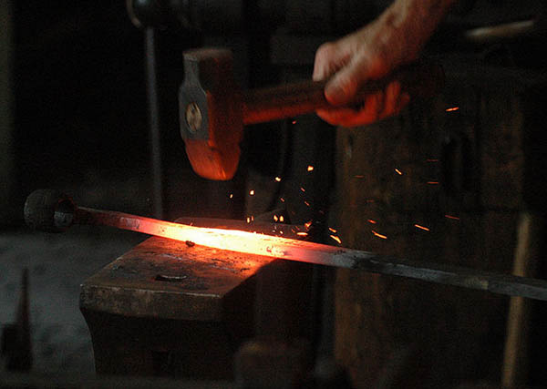 A blacksmith hammering iron