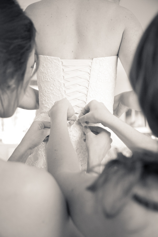 Tieing the ribbon on the back of the wedding dress