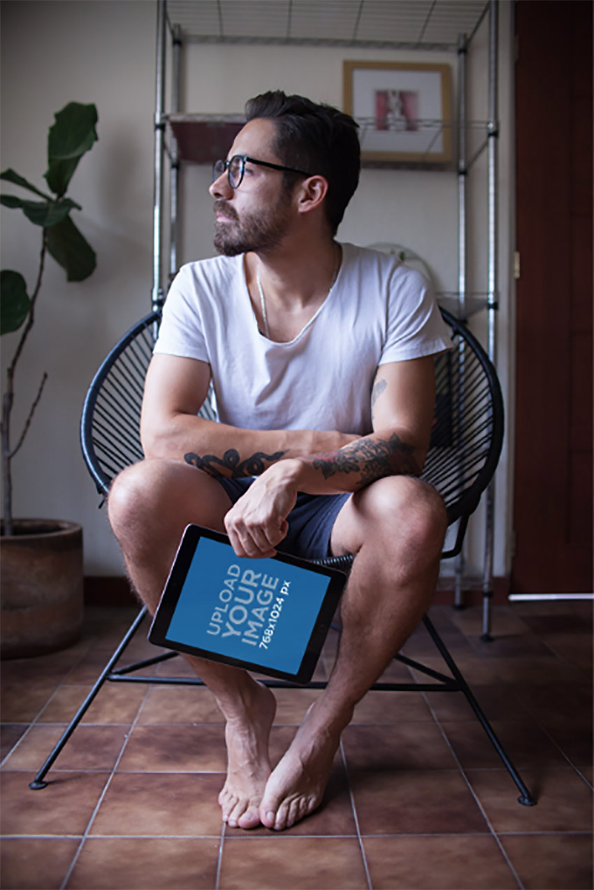 iPad Mockup Featuring a Man sitting on an Acapulco Chair