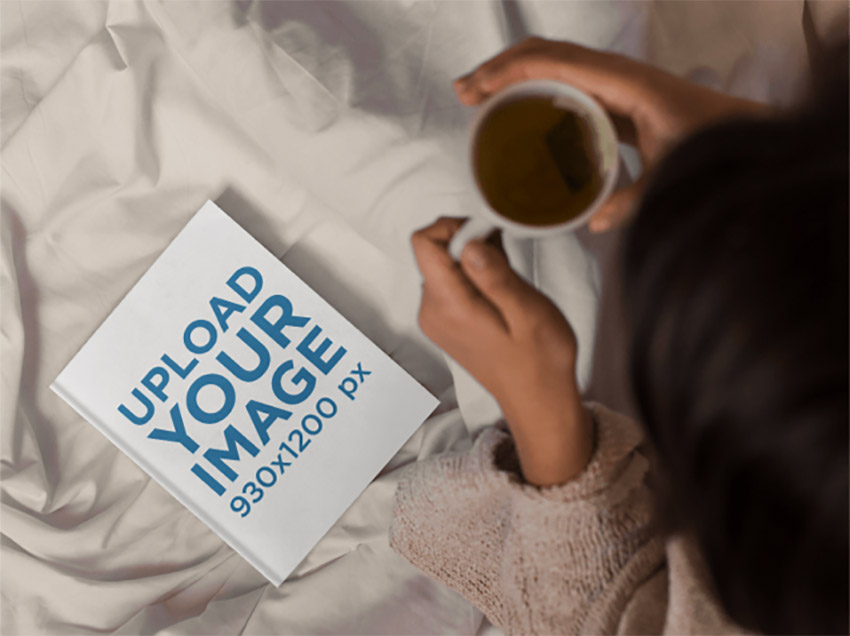 Mockup From Above of a Girl Reading a Book and Drinking a Tea While in Bed