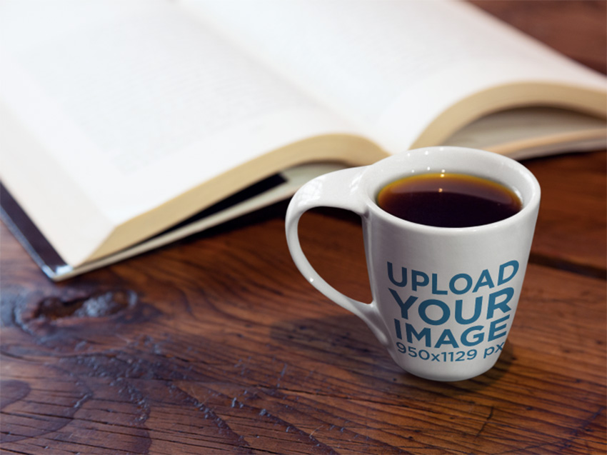 Cup Mockup of a Cup Standing Next to a Book on Top of a Desk